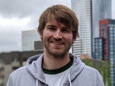 Photo of a man in a hooded sweatshirt against the Seattle skyline