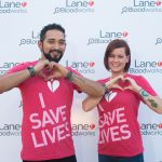 "Image of a man and a woman wearing shirts that say ""I save lives"" making their hands into hearts"